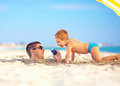 Happy father and son talking on smart phone together on the beach smartphone Royalty Free Stock Photography