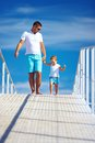 Happy father and son walking on blue sky horizon together Royalty Free Stock Images