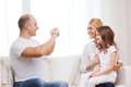Happy father taking picture of mother and daughter family child photography home concept smiling Stock Photo