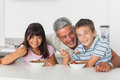 Happy father talking with his children during their breakfast in kitchen Royalty Free Stock Images