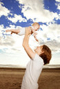 Happy father throws up baby boy against blue sky and white clouds Royalty Free Stock Photo