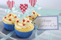 Happy fathers day bright and cheery red white and blue decorated cupcakes closeup with heart toppers gift tag on vintage shabby Stock Images