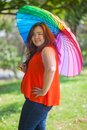 Happy fatty woman with umbrella asian outdoor in a park Royalty Free Stock Images
