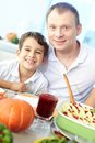 Happy feast portrait of boy and his father sitting at festive table and looking at camera Royalty Free Stock Photos