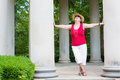 Happy feel good grandma trendy modern leaning with outstretched arms between two columns celebrating the sunshine and nature with Royalty Free Stock Images