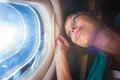 Happy female airplane passanger enjoying the view from the cabon window over the blue sky shallow dof intentional flare Royalty Free Stock Image