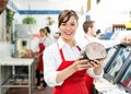 Happy female butcher holding large ham portrait of at store with colleagues working in background Royalty Free Stock Images