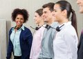 Happy female call center employee standing with portrait of team at Stock Photo