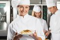 Happy female chef presenting dish portrait of with colleagues in background Stock Image