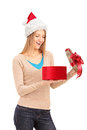Happy female with christmas hat opening a gift Royalty Free Stock Image