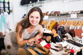 Happy female customer selecting shoes in footgear center Royalty Free Stock Photo