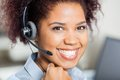 Happy female customer service representative closeup portrait of wearing headset in office Royalty Free Stock Photo