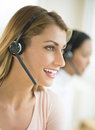 Happy female customer service representative wearing headset close up of with colleague in background Stock Images