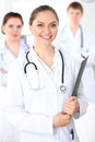 Happy female doctor keeping medical clipboard while medical staff are at the background Royalty Free Stock Photo