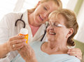 Happy female doctor nurse explaining prescription to senior adult woman Royalty Free Stock Photos