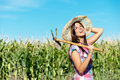 Happy female farmer in corn field successful carrying hoe and smiling countryside woman with work tool wearing straw hat and Stock Photo