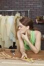 Happy female fashion designer looking away while holding eyeglasses Stock Photo
