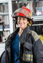 Happy female firefighter standing against portrait of firetruck at station Stock Images