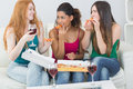 Happy female friends eating pizza with wine at home young on sofa Stock Photo