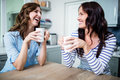 Happy female friends holding coffee mugs while discussing at table Royalty Free Stock Photo