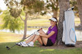 Happy female golfer taking a break beautiful hispanic and sitting under tree Stock Images