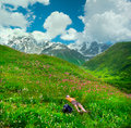 Happy female hiker lying on the meadow icy peaks background Stock Photography