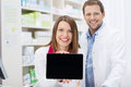 Happy female pharmacist doing a promotion displaying the blank screen of tablet pc to the camera as she stands in the pharmacy Stock Image