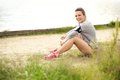 Happy female runner resting young looking while at a lake Stock Photos