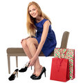 Happy female shopper choosing shoes beautiful stylish a pair of new high heeled sitting on a bench in the store with her shopping Royalty Free Stock Image