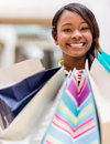Happy female shopper holding shopping bags and smiling Royalty Free Stock Photos