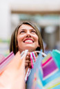 Happy female shopper looking up and holding bags Royalty Free Stock Photo