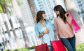 Happy female shoppers looking very carrying bags Royalty Free Stock Images