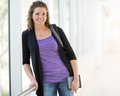 Happy female student with digital tablet and portrait of backpack standing at university corridor Stock Photo