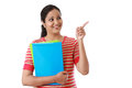 Happy female student holding text book and showing copy space Royalty Free Stock Photo