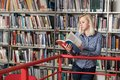 Happy Female Student Reading from Book in Library