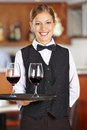 Happy female waiter with wine glasses two red in a restaurant Royalty Free Stock Photo