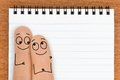 Happy finger face couple with blank notepad copy space for Stock Images