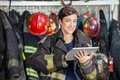 Happy firewoman holding digital tablet at fire portrait of in uniform station Royalty Free Stock Photography