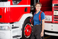 Happy firewoman holding helmet against firetruck portrait of while standing at station Stock Photos