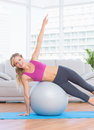 Happy fit blonde doing side plank with exercise ball at home in the living room Stock Photography