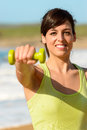 Happy fitness woman with dumbbell working out on beach in summer sporty girl lifting weights and punching outdoor caucasian Stock Image