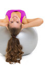 Happy fitness young woman doing abdominal crunch on fitness ball rear view Stock Image
