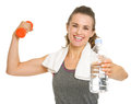 Happy fitness young woman holding dumbbells and giving bottle of water Royalty Free Stock Photos
