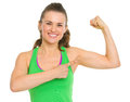 Happy fitness young woman pointing on biceps isolated white Royalty Free Stock Photo