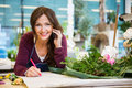 Happy florist taking order in flower shop portrait of female using mobile phone while writing on paper Stock Images