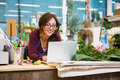 Happy florist using laptop at counter in flower mid adult female shop Stock Images