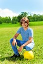 Happy football portrait of years old boy sit on squads with ball on the field on bright sunny day Stock Photography