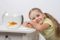 Happy four-year girl put her head in his hands sitting in front of a goldfish Royalty Free Stock Photo