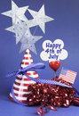 Happy fourth th of july party table decorations with hat streamers sign flag and stars in usa america red white and blue theme Royalty Free Stock Photography