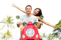 Happy free freedom couple driving scooter excited on summer holidays vacation young multiethnic in love asian woman Royalty Free Stock Images